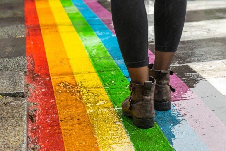 legs walking on lgbtq rainbow crosswalk