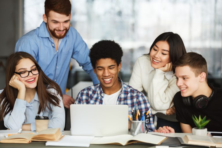 happy students watching tutorial videos on laptop