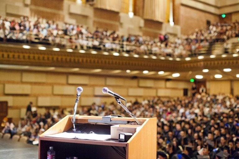 empty microphone podium overlooking a full auditorium