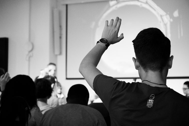 back of a person's head as they raise their hand from the audience during an event