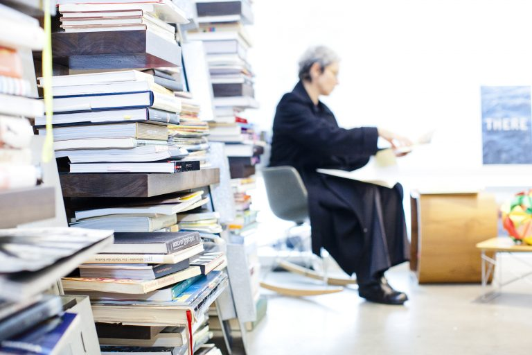 professor in her office surrounded by books and papers