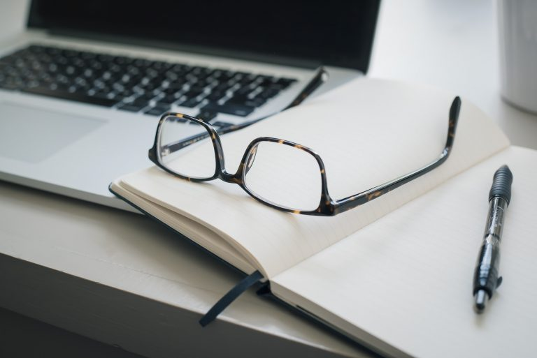 a pair of glasses and a pen on top of an empty notebook, all lying on a table near a laptop